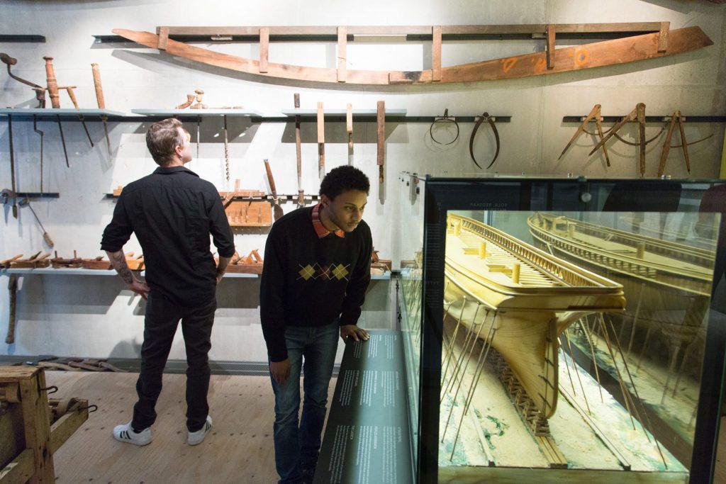 Två unga män syns på bilden. Längst till vänster och längre bak står en vit man i svarta kläder med ryggen bortvänd mot kameran och tittar uppåt, lite åt höger på verktyg som använts till att bygga skepp som är uppställda på rad på en vit vägg. En ung svart man i svart tröja och jeans står längre fram, i mitten på bilden, och studerar en monter där man ser en modell av ett fartyg som ska föreställa vara i byggnadsskede.