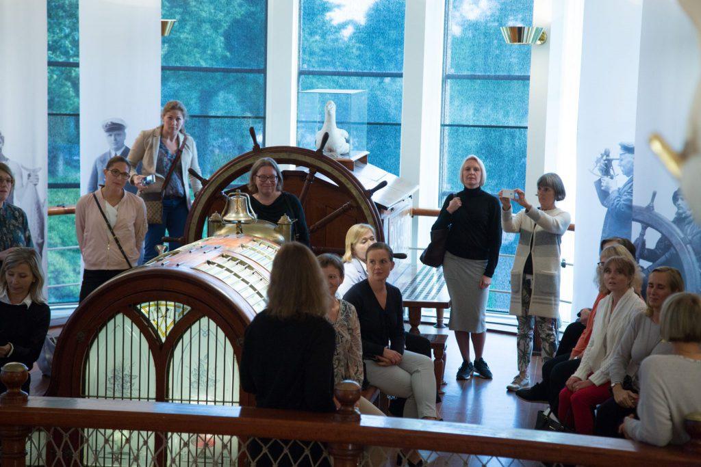 En grupp vita människor, de flesta blonda kvinnor, står på en plats föreställande ett poopdäck på en båt. Där finns en ett par kvinnor t