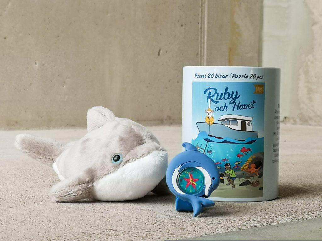 """Längst till höger finns en porslinsburk som innehåller ett 20-bitars pussel, med en bild av en båt och en vit råtta i flytväst som fiskar från båtens för. Ovanför syns texten """"Ruby och havet"""". Framför burken finns en liten grön klocka med röd mitt och gula visare, där en blå delfin böjd i en cirkel pryder klockan som ram. Längst till vänster finns en grå delfin med blå ögon som mjukisdjur. Bakgrunden är ljus, mattgolv och träväggar."""