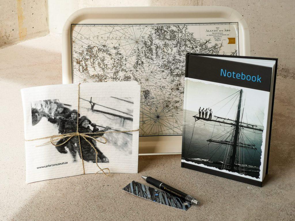 """Mot en ljus bakgrund står ett urval av svartvita föremål. Längst till vänster finns en disktrasa med sjömän i regnrockar och sydvästar stående på enj diagonal rad som motiv. Disktrasan har ett brunt snöre runt sig, bundet som ett paket och med rosett. Längst till höger finns en inbunden bok, lite öppnad så den kan stå själv. På boken står """"Notebook"""" på i koboltblått på en svart rad, och under det en småbåtshamn och en mast längst fram som motiv. Längst bak finns en bricka med ett sjökort som motiv. Längst fram finns ett svart bokmärke med vita ränder och en svart bläckpenna."""