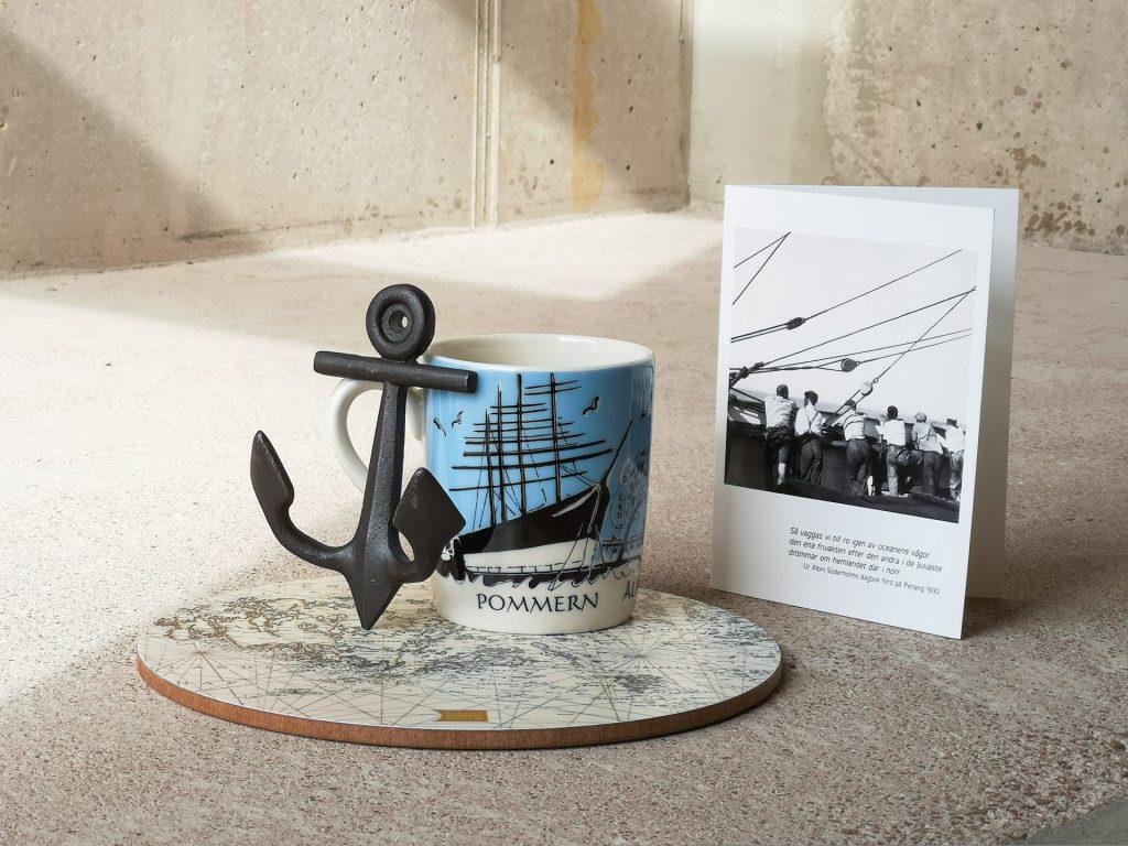 I mitten på bilden syns en porslinsmugg med ljusblå balgrund med Pommern som motiv. Till vänster om den finns ett prydnadsankar i metall. De båda föremålen står på ett runt grytunderlägg som har ett sjökort som motiv. Till höger om föremålen står ett vykort med svartvitt fotografi föreställande sjömän, vända bort från kameran, och tittar över ett skepps reling. Under fotografiet står en oläsbar dikt. Föremålen är ställda på en ljus bakgrund med matta som golv och väggar i trä.