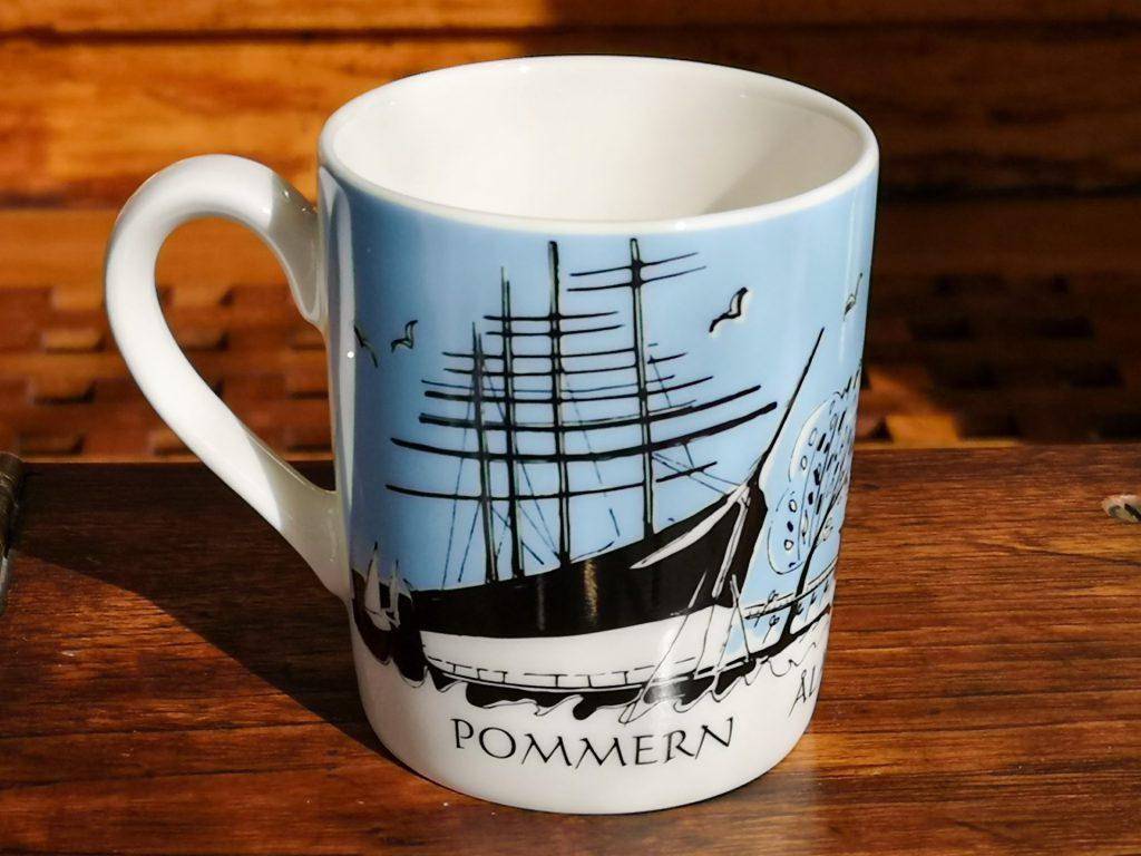"""Mot en bakgrund i mörkt trä syns en vit porslinsmugg med ljusblå bakgrund på själva koppdelen och ett segelfartyg tecknad i svart och lite gulbrunt snett framifrån utan segel. Under skeppet står det """"POMMERN""""."""