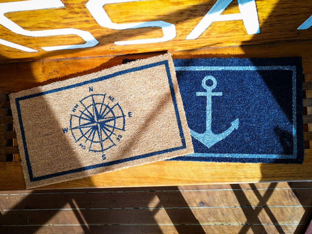 """På en träig bakgrund syns två dörrmattor delvis. Till vänster finns en ljusbrun matta med mörkblå ram och kompass som motiv. Delvis under den och till höger finns en mörkblå matta med ljusblå ränder uppe och nere samt ett ankare som motiv. Mattorna ligger på en bänk av ljusare träfärg än golvet. Längst upp på bilden syns bokstäverna """"SSA"""" delvis."""