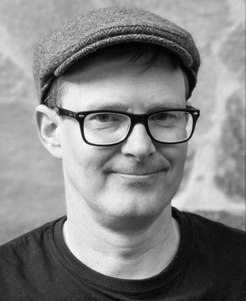 Ett svartvitt porträttfoto taget snett framifrån på en medelålders, leende man med runt ansikte. Han har ljust hår under en mellangrå keps av flat cap-typ, tjocka svarta glasögonbågar och mörk T-shirt.