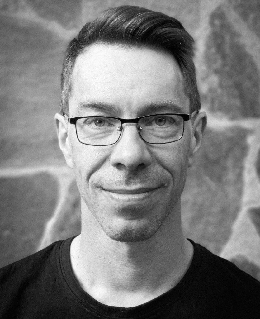 Ett svartvitt porträttfoto taget rakt framifrån på en medelålders, leende man med smalt ansikte, glasögon och kortklippt mörkt hår. I nedre kanten syns hans mörka T-shirt.