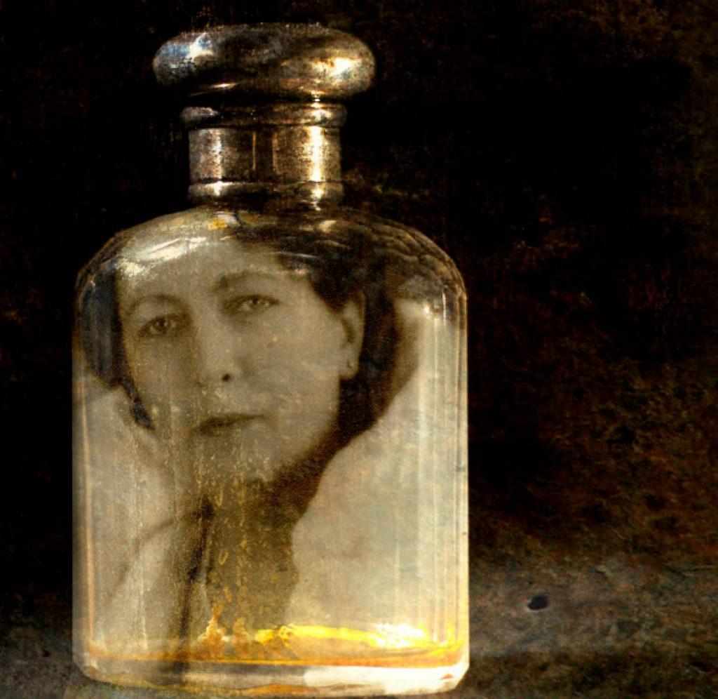 Ett gammalt foto på en medelålders kvinna med kort mörkt hår, föreställande Hilda Erikson, vars porträtt är anpassat att passa i flaskdelen av en parfymflaska. Flaskan har en mörk kork i metall och står mot mörk bakgrund. Flaskan står lite till vänster om mitten.