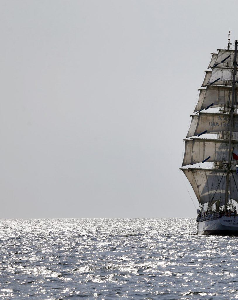 Längst på bildens högra sida syns ett segelfartyg delvis. Bilden är tagen bakom båtens akter och sex segel per mast syns, men endast en mast syns. Båten är på en rand av glittrande hav, resten av bakgrunden är ljusblå himmel.