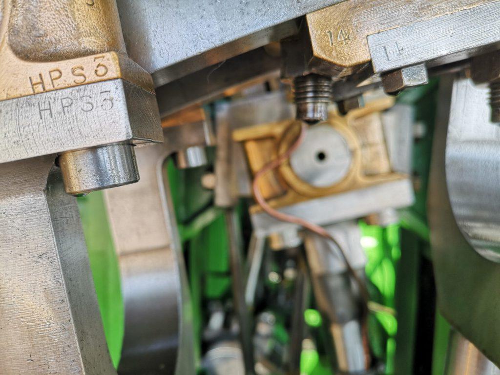 """Detaljbild av maskineri. På bildens övre halva syns grå och beige maskindelar, mest rektangulära delar, i högra hörnet en femhörnig polygon, ett par olika utstickande muttrar och skruvar från sidan, samt en cirkel som är har gula sladdar runt sig. Grå och svarta rör löper neråt från cirkeln, som är strax till höger av bildens mitt. Bakom rören syns gröna maskindelar. Till vänster syns en maskindel som är randig i grått, svart och grönt från vänsters nedre kant i den ordningen. I vänstra övre hörnet sticker det ut en rektangulär bit i först mässingkub, en tunn rand mässing, en gråmetallisk kub, och två rör i respektive färg. På mässingsranden står """""""