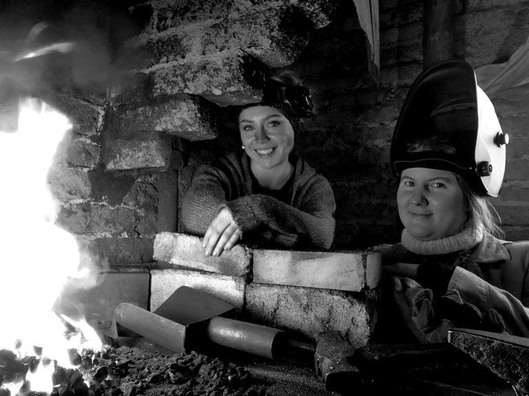Metallkonstnärerna Olivia Sarling och Ulrika Kjeldsen vid en öppen eldstad.